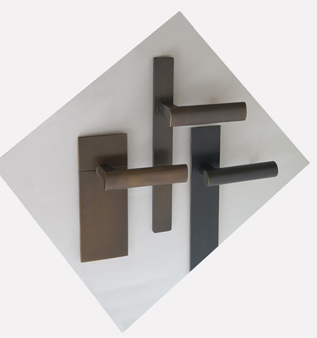 Three modern and minimalist door handles in dark finishes on oversized backplates.